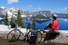 Bicycle in view of Wizard Island in the deep blue lake at Crater Lake National Park in early June when Rim Drive is closed to cars to allow snow plowing, Oregon, USA.