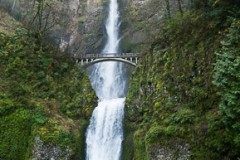 Multnomah Falls plunges 620 feet in two tiers in Columbia River Gorge National Scenic Area, adjacent to Interstate 84 and Historic Columbia River Highway, in Oregon, USA. A foot trail leads to Benson Footbridge, a 45-foot (14 m) long footbridge that allow